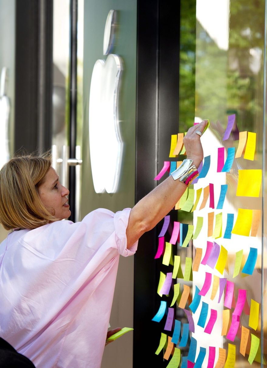 ROD LAMKEY JR./THE WASHINGTON TIMES Maha Akkad of Fort Smith, Ark., places a note paying tribute to Apple co-founder Steve Jobs on the window of an Apple Store in Arlington on Thursday.
