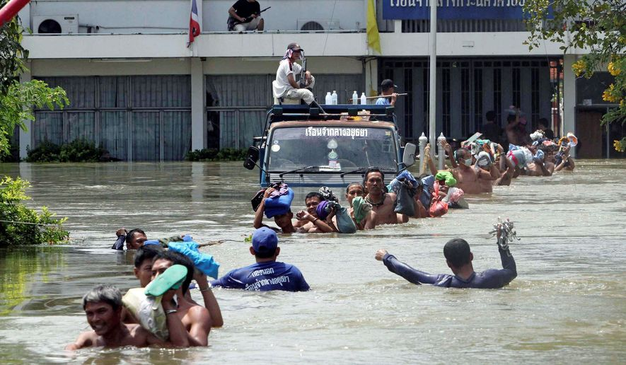 ASSOCIATED PRESS Prisoners at Ayutthaya province prison in central Thailand wade in chest-deep water to board a bus Thursday during an evacuation as storms continue to flood the area. Other countries in Southeast Asia also have endured the worst flooding in 50 years.