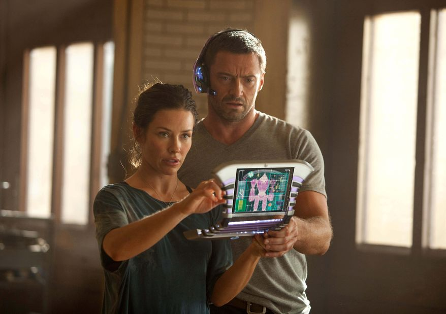 """Evangeline Lilly as Bailey, in a scene with Hugh Jackson, is the go-to person when robots need repairs after their bouts in """"Real Steel,"""" rated PG-13 for mild profanity and robot mayhem. (Disney/Dreamworks II photograph via Associated Press)"""