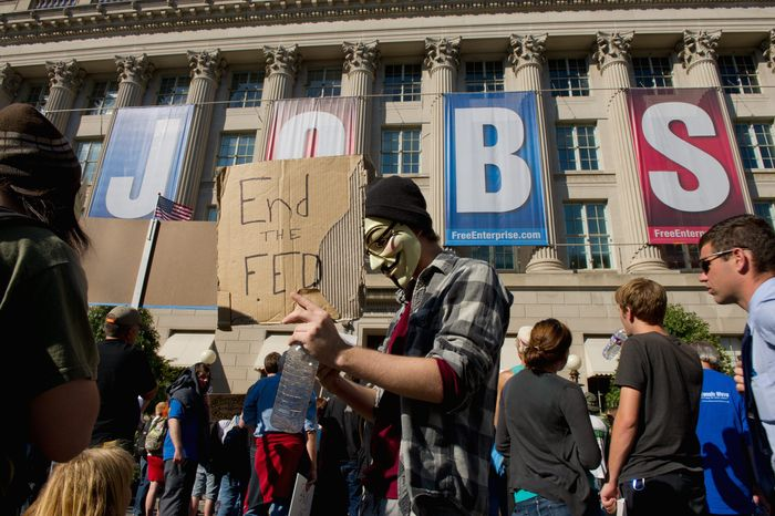 Barry Freed wears a mask of 17th-century Gunpowder Plotter Guy Fawkes in a protest Thursday outside the Chamber of Commerce. (Andrew Harnik / The Washington Times)