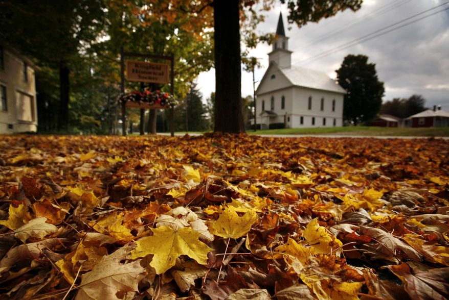 **FILE** Fallen maple leaves carpet a lawn across the street from the First Baptist Church of Kingfield, Maine, on Sept. 30, 2011. As trees start showing autumn's golden, orange and red hues, nature lovers aren't the only ones taking note: Scientists are watching trees and making note of time that leaves change and drop as they seek to determine climate change's impact. (Associated Press)