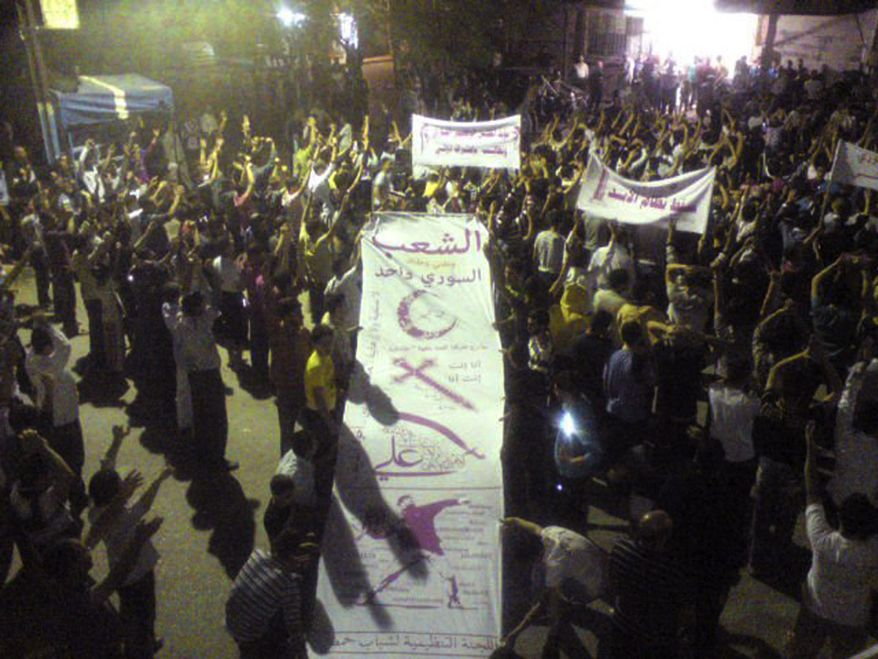"Demonstrators against the regime of Syrian President Bashar Assad hold a banner with the Muslim crescent, Christian cross, Alawite-sect sword, the name of Imam Ali, and the Arabic words ""The Syrian people is one"" on Monday, Oct. 3, 2011, in Homs, Syria. (AP Photo/Citizen journalist via the Union of Homs City Neighborhood)"