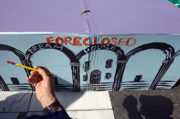 """Protester Andy Shallal of Washington paints """"Foreclosed"""" on a cardboard house as hundreds of protesters gather at Freedom Plaza before marching to the White House in Washington on Thursday, Oct. 6, 2011. (Andrew Harnik/The Washington Times)"""