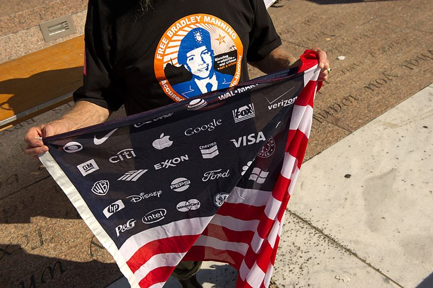 Protester Bob Bowes from Somerville, Massachusetts holds an american flag which has corporate logos instead of starts at a protest for a variety of issues from the ongoing wars in Afghanistan and Iraq to corporate greed and jobs at Freedom Plaza in Washington, DC, October 6,  2011. (Andrew Harnik / The Washington Times)