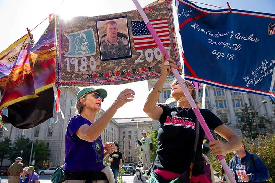 """Protesters Emily Keel, left, of Robersonville, North Carolina and Kit Kittridge, right, of Quilcene, Washington with Code Pink set up a """"Peace Ribbon"""" in Freedom Plaza which honors those who have lost their lives in Afghanistan and Iraq, Washington, DC, October 6,  2011. Hundreds of protesters upset about a variety of issues from the ongoing wars in Afghanistan and Iraq to corporate greed and jobs at Freedom Plaza before marching to the White House, Chamber of Commerce and along K Street in Northwest. (Andrew Harnik / The Washington Times)"""