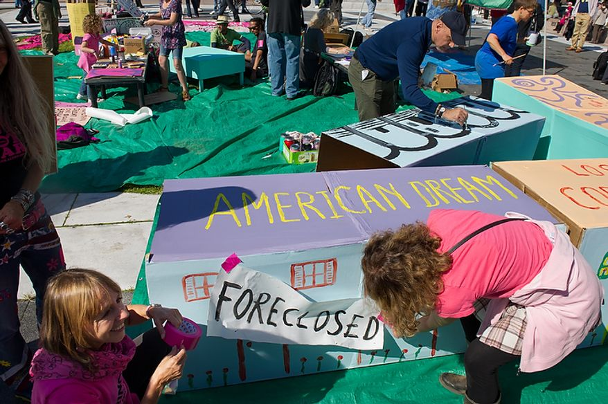 Code Pink protesters Medea Venjamin, left, tapes up a foreclosure sign on a painted cardboard house while hundreds of protesters, upset about a variety of issues from the ongoing wars in Afghanistan and Iraq to corporate greed and jobs, gather at Freedom Plaza before marching to the White House, Chamber of Commerce and along K Street in NW Washington, DC, October 6,  2011. (Andrew Harnik / The Washington Times)