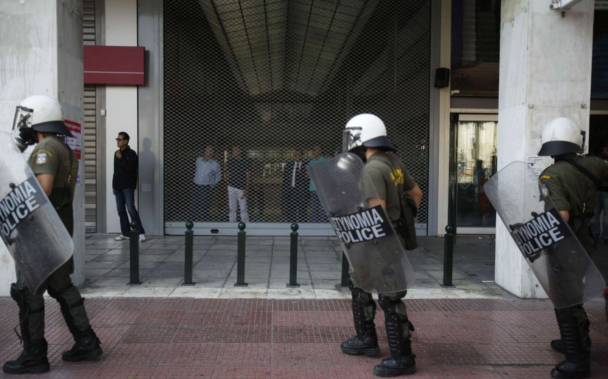 In this Wednesday, Oct. 5, 2011, photo riot police walk past the rolled down shutter of a shopping alley in Athens during a protest. Central Athens sees major avenues and roads blocked and traffic diverted by protests nearly every day. (AP Photo/Dimitri Messinis)