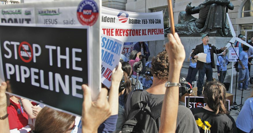 Mike Tidwell (right) from the Chesapeake Climate Action Network addresses a rally outside the Ronald Reagan Building in Washington on Oct., 7, 2011, against the proposed Keystone XL pipeline. (Associated Press)