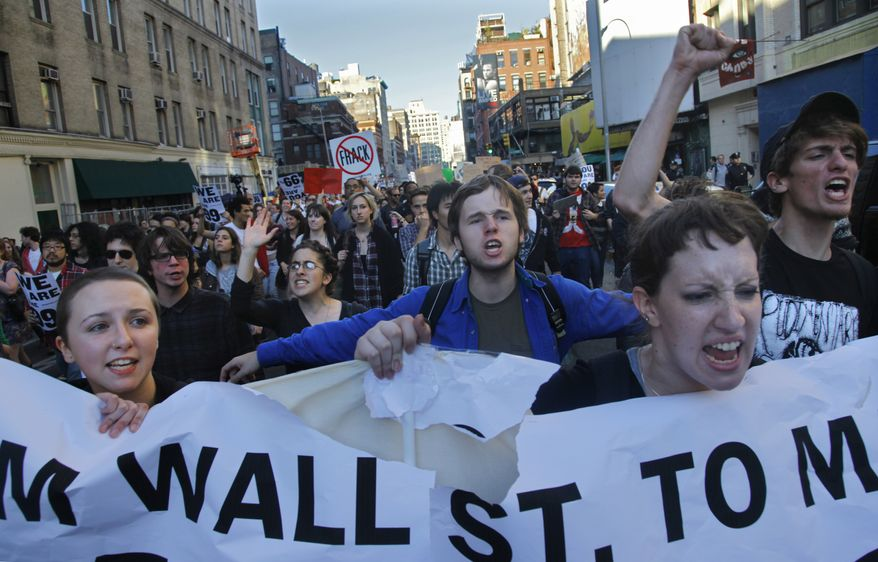 """A coalition of students and their supporters from New York University and The New School chant """"show me what democracy looks like"""" as they march towards Zuccotti Park in lower Manhattan during the Occupy Wall Street protests on Oct. 5, 2011. (Associated Press)"""