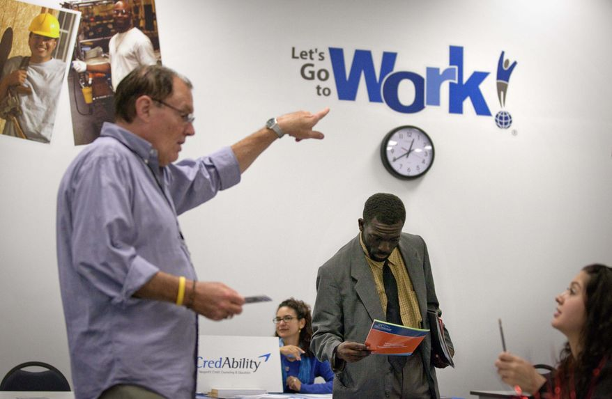 In this Oct. 4, 2011, photo, Snotti St. Cyr, center, looks over a brochure while attending a job fair at a Goodwiill store in Atlanta. The number of people who applied for unemployment benefits rose slightly last week, a sign that the job market remains weak. (AP Photo/David Goldman)