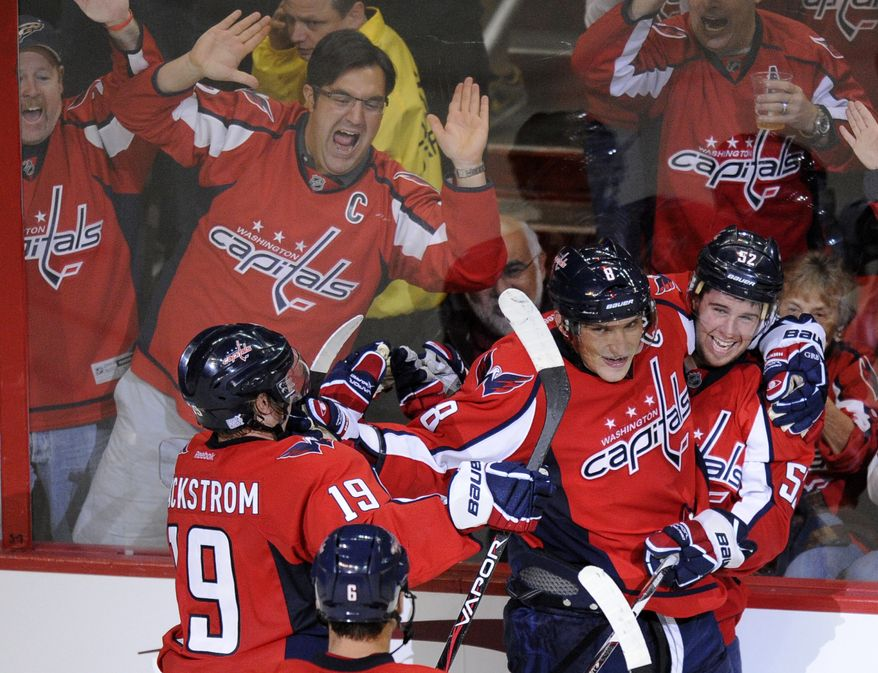 Washington Capitals defenseman Mike Green, right, celebrates his game-winning goal with teammates Alex Ovechkin and Nicklas Backstrom during overtime against the Carolina Hurricanes on Saturday, Oct. 8, 2011, in Washington. The Capitals won 4-3 in overtime. (AP Photo/Nick Wass)