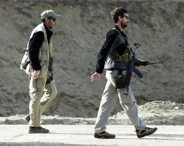 ** FILE ** Two men with U.S. special operations forces walk nearby as the Northern Alliance troops fight pro-Taliban forces in the fortress near Mazar-e-Sharif in northern Afghanistan in 2001. (AP Photo/Darko Bandic, File)
