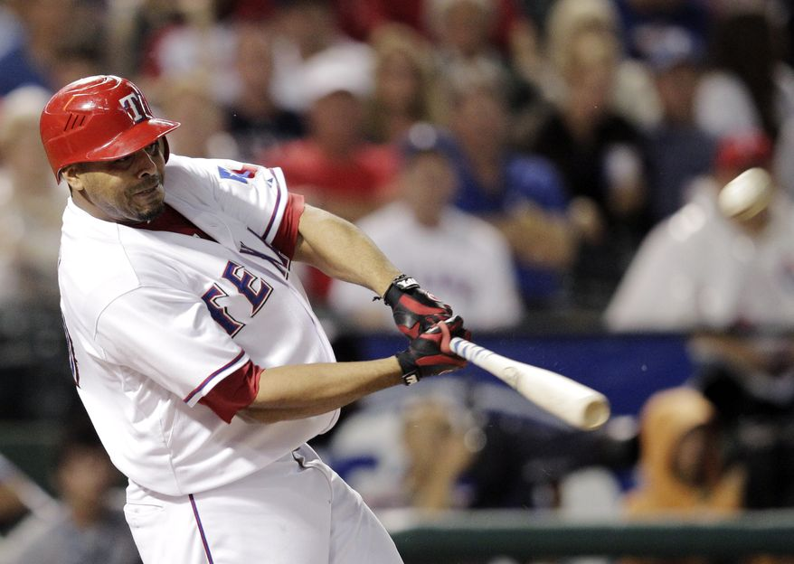 Texas Rangers' Nelson Cruz hits a solo home run against the Detroit Tigers during Game 1 of baseball's American League championship series Saturday, Oct. 8, 2011, in Arlington, Texas. (AP Photo/Charlie Riedel)
