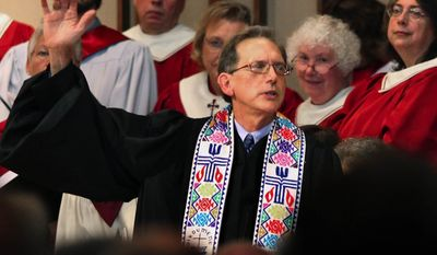 The Rev. Scott Anderson gives the benediction at the end of his ordination ceremony in Madison, Wis., on Saturday, Oct. 8, 2011. Mr. Anderson is the first openly gay person to be ordained to the ministry in the Presbyterian Church (U.S.A.), the nation's largest Presbyterian church. (AP Photo/Wisconsin State Journal, Craig Schreiner)