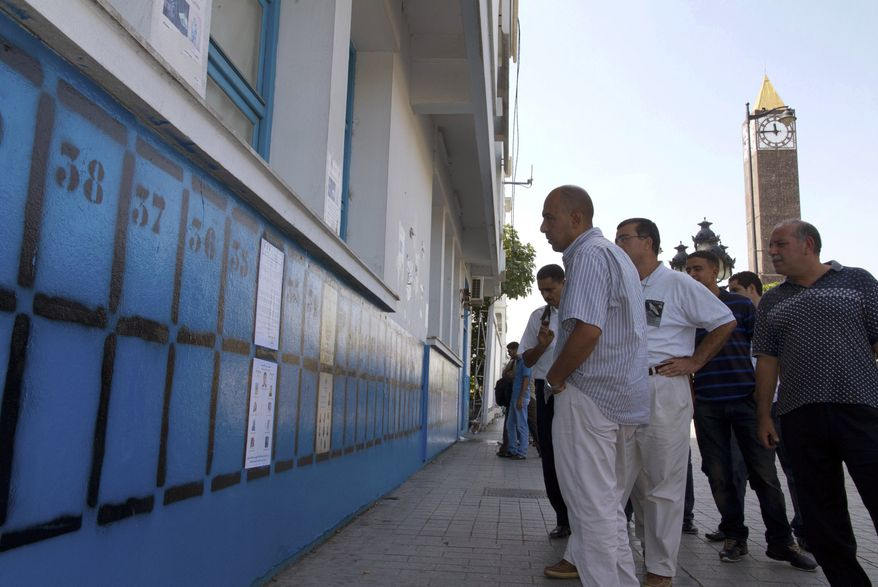 Tunisians look at election posters in Tunis, Tunisia, on Saturday, Oct. 1, 2011. (AP Photo/Amine Landoulsi)