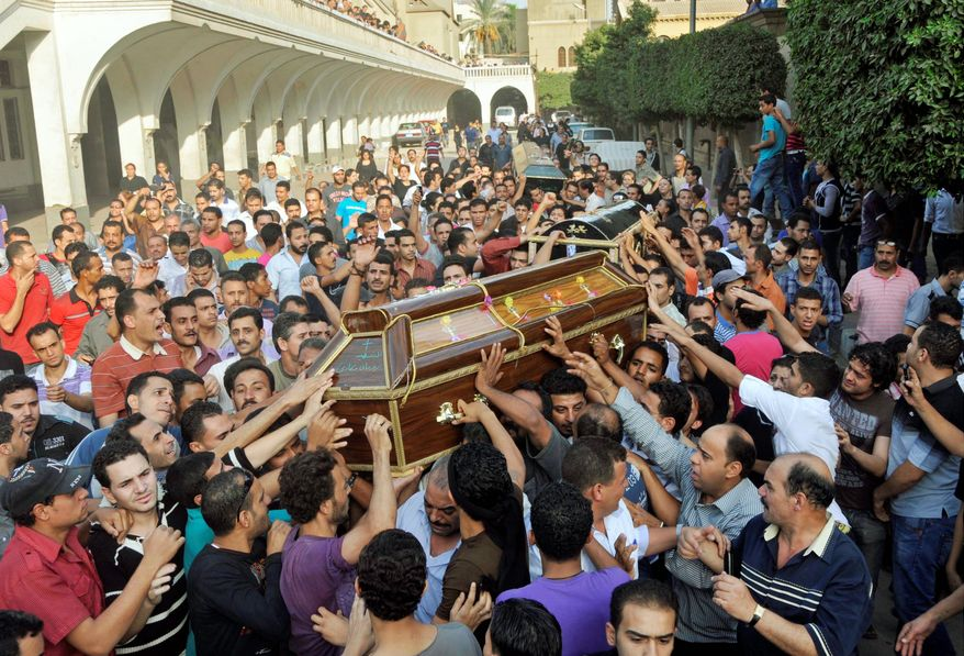 Mourners carry the coffin of victims of clashes between protesters and security forces in Cairo on Monday. (Associated Press)