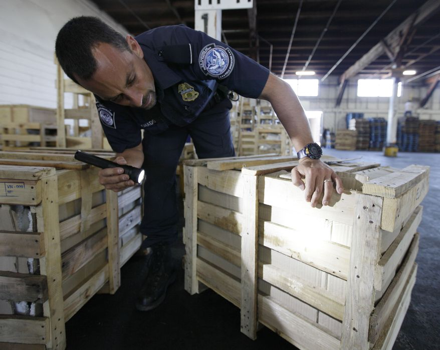 Agriculture specialist John Machado, with U.S. Customs and Border Protection, spots during an inspection in Oakland, Calif., on Aug. 23, 2011, a wooden crate into which a pest had bore. (Associated Press)