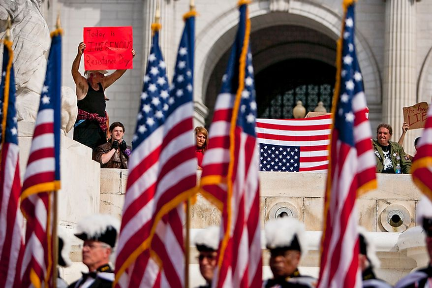 Protesters hold signs condemning the version of American history that paints Christopher Columbus in a glowing light during a Columbus Day celebration and wreath presentation at Union Station in Washington on Monday, Oct. 10, 2011.  (T.J. Kirkpatrick/The Washington Times)