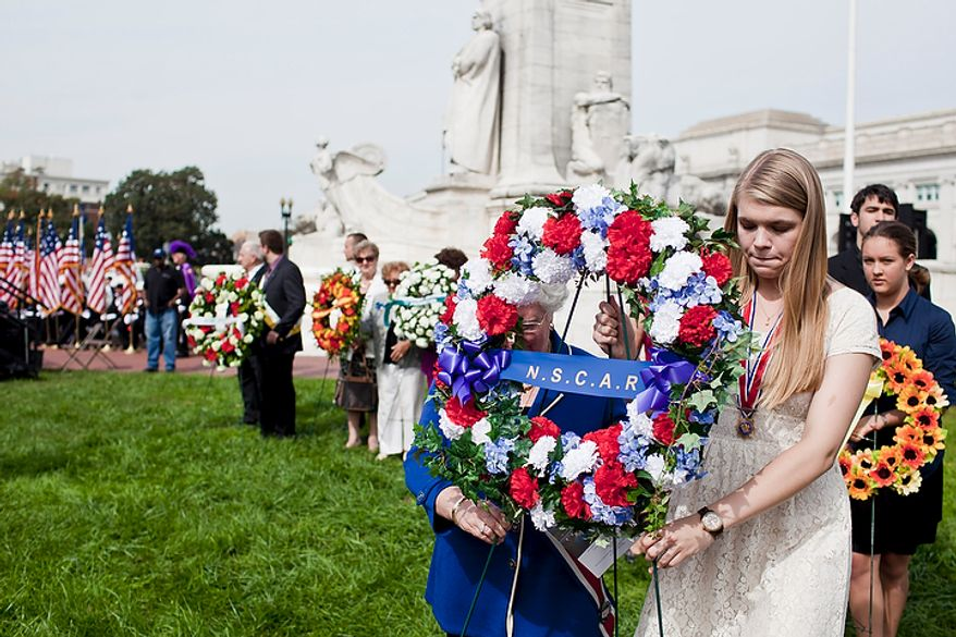 Mary Lib Schmidt (right) and Anne Schaeffer carry a wreath from the National Society of the Children of the American Revolution during a Columbus Day celebration and wreath presentation at Union Station in Washington on Monday, Oct. 10, 2011. (T.J. Kirkpatrick/The Washington Times)