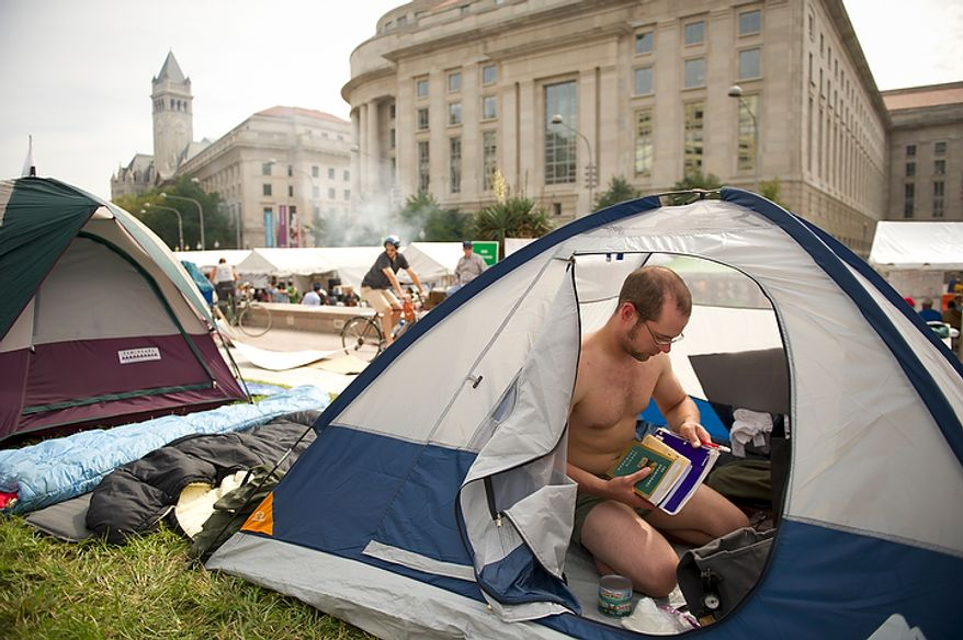"""Jacob Griesmer of Mosinee, Wisc., organizes his things inside his tent during a protest affiliated with the """"Occupy D.C."""" movement at Freedom Plaza in Washington, D.C., Monday, October 10, 2011. Mr. Griesmer made the trip from Wisconsin to join the protest. (Rod Lamkey Jr/The Washington Times)"""
