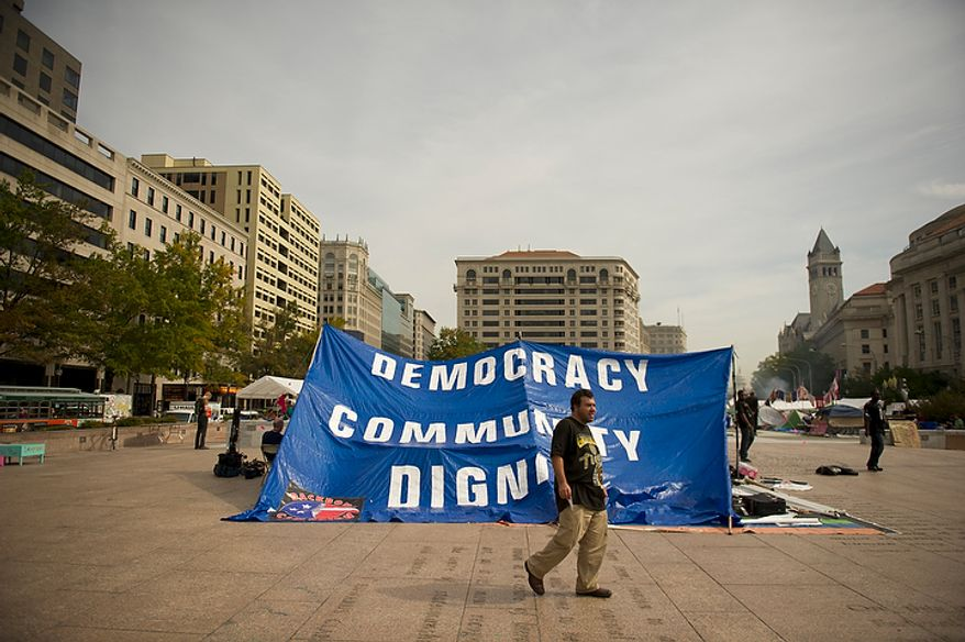 """A man walks past a large banner during a protest affiliated with the """"Occupy D.C."""" movement at Freedom Plaza in Washington, D.C., Monday, October 10, 2011. This protest which began here last week has occupied prime real estate in the nation's capitol with tents and sleeping bags. (Rod Lamkey Jr/The Washington Times)"""