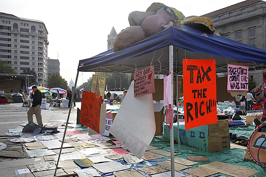 People start to move about Freedom Plaza in Washington, Monday, Oct. 10, 2011, among protest signs, as part of a protest against the war and corporate America. (AP Photo/Jacquelyn Martin)