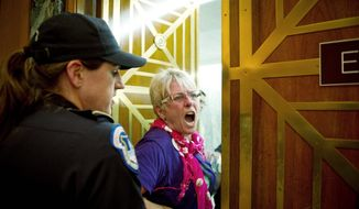 A protester is removed Tuesday from the Senate Finance Committee's markup of trade agreements with South Korea, Colombia and Panama on Capitol Hill. Congress is expected to pass the pacts Wednesday. (Rod Lamkey Jr./The Washington Times)