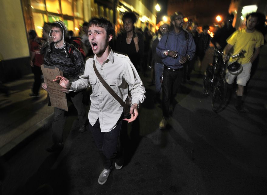 """Demonstrators with """"Occupy Boston"""" march toward a police station where fellow demonstrators were taken after police arrested people sleeping in an expansion of the protesters' tent village in Boston in the early morning hours of Tuesday, Oct. 11, 2011. (AP Photo/Josh Reynolds)"""