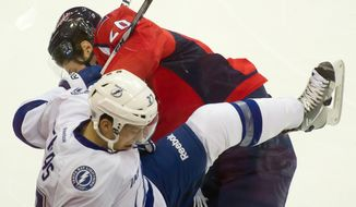 Troy Brouwer (20) of the Washington Capitals slams Bruno Gervais (27) of the Tampa Bay Lightning against the glass in the second period at the Verizon Center in Washington, D.C., Oct. 10, 2011. (Andrew Harnik/The Washington Times)