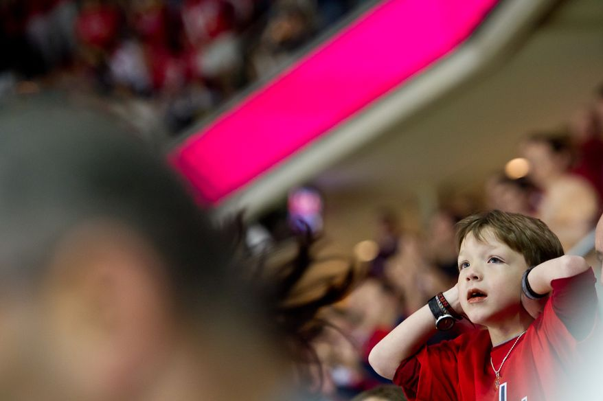 A young fan covers his ears as other fans react to a goal during the first period as the Washington Capitals take on the Tampa Bay Lightning at the Verizon Center in Washington, D.C., Oct. 10, 2011. (Andrew Harnik/The Washington Times)