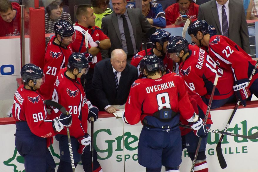 Washington Capitals head coach Bruce Boudreau, center, talks to his team during a time out in overtime against the Tampa Bay Lightning at the Verizon Center in Washington, D.C., Oct. 10, 2011. (Andrew Harnik/The Washington Times)