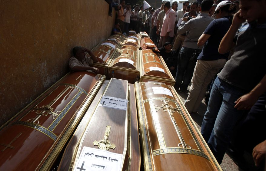 Egyptians are gathering around the coffins of 17 of the Copts who were killed during clashes with the Egyptian army late Sunday, outside the morgue of the Copts hospital in Cairo, Egypt, Monday, Oct. 10, 2011. (AP Photo/Khalil Hamra)