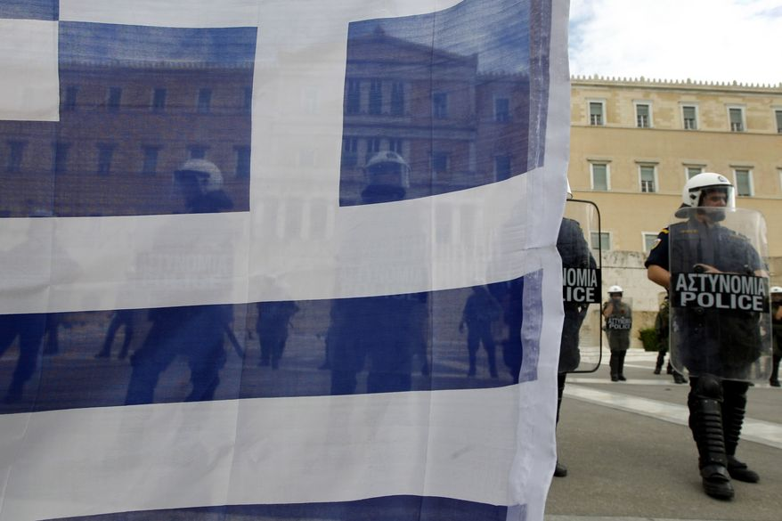 Riot police stand guard outside the Greek parliament, seen through a Greek flag held by a protester, during a civil-servant protest in Athens on Tuesday, Oct. 11, 2011. (AP Photo/Petros Giannakouris)