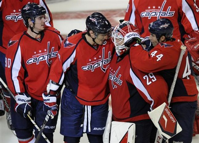 Washington Capitals goalie Tomas Vokoun (29), of the Czech Republic is celebrates with teammates Marcus Johansson (90), of Sweden, Alex Ovechkin (8), of Russia, and Roman Hamrlik (44), of the Czech Republic, after they defeated the Tampa Bay Lightning 6-5 in a shootout in an NHL hockey game, Monday, Oct. 10, 2011, in Washington. (AP Photo/Nick Wass)