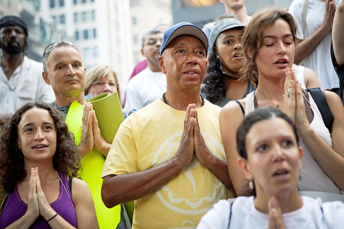 """Russell Simmons (center), co-founder of Def Jam records, participates in a yoga session in collaboration with the """"Occupy Wall Street"""" protests in New York's Zuccotti Park. (Associated Press)"""