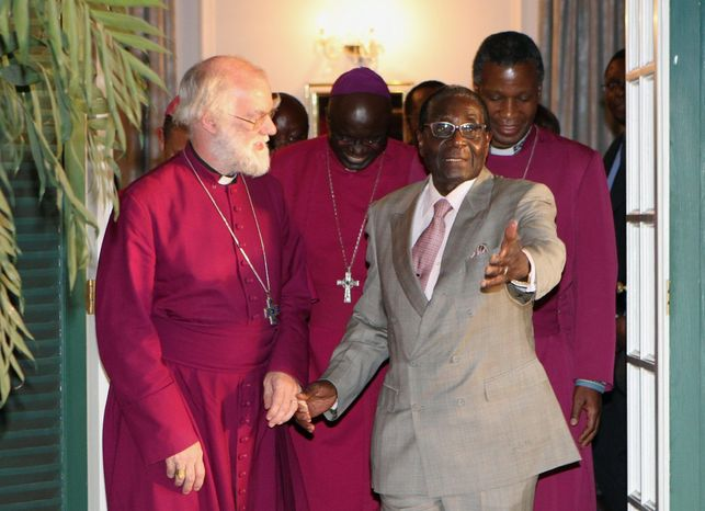 The Archbishop of Canterbury Rowan Williams (left) meets with Zimbabwean President Robert Mugabe at the State House in Harare, Zimbabwe, on Monday to deliver a report detailing incidents of intimidation at Anglican churches. (Associated Press)
