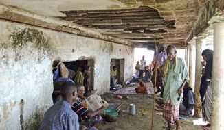 Displaced families who fled famine in Somalia a couple of months ago take shelter in a destroyed building after moving out of their makeshift tents, which became flooded by rains, in Mogadishu, Somalia. Fighting broke out there over the weekend, killing at least 20. (Associated Press)