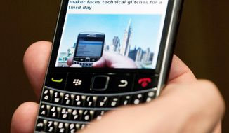 A subscriber holds a BlackBerry in Ottawa. (Associated Press)