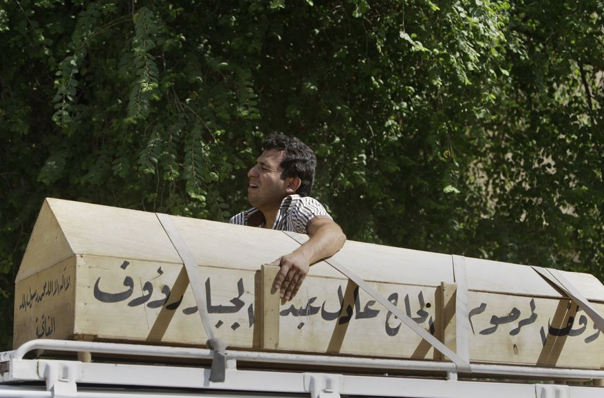 Alaa Mohammed grieves over the coffin of his brother, Iraqi policeman Sattar Mohammed, in Baghdad on Wednesday, Oct. 12, 2011. A slew of bombings targeting police in the capital killed 25 people and wounded scores of others, police said. (AP Photo/Karim Kadim)