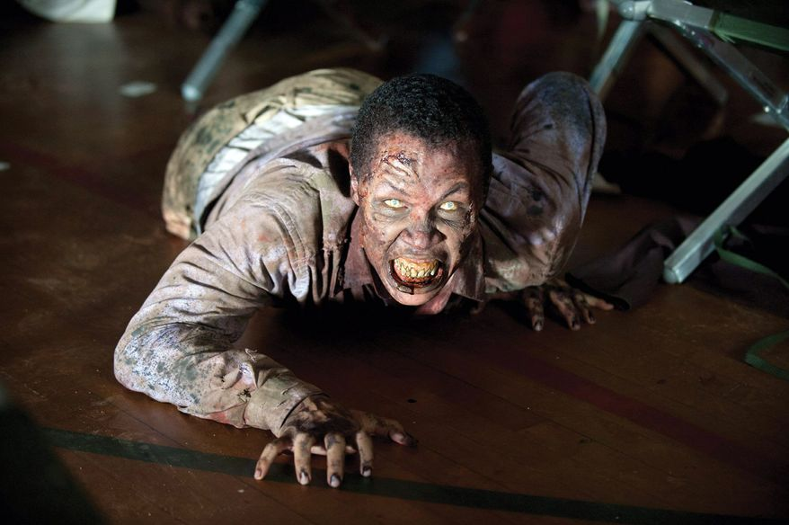 "A zombie from the second season of AMC's ""The Walking Dead,"" premiering Sunday, crawls onto the set in picturesque rural Georgia. Special-effects prosthetic makeup won designer Greg Nicotero an Emmy last year. (AMC via Associated Press)"