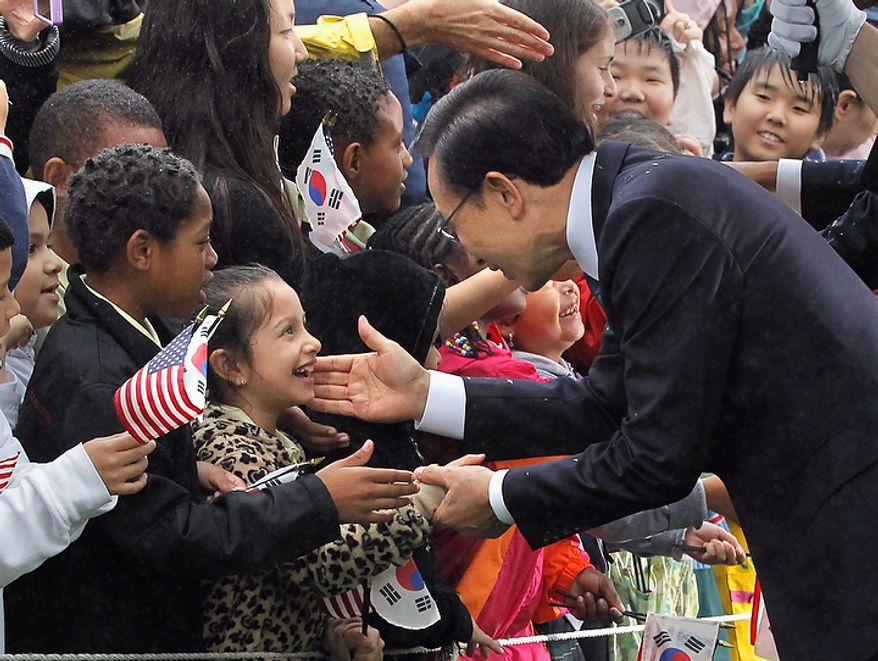 South Korean President Lee Myung-bak reaches out to local schoolchildren during a rainy state arrival ceremony with President Obama on Thursday, Oct. 13, 2011, on the South Lawn of the White House in Washington. (AP Photo/J. Scott Applewhite)