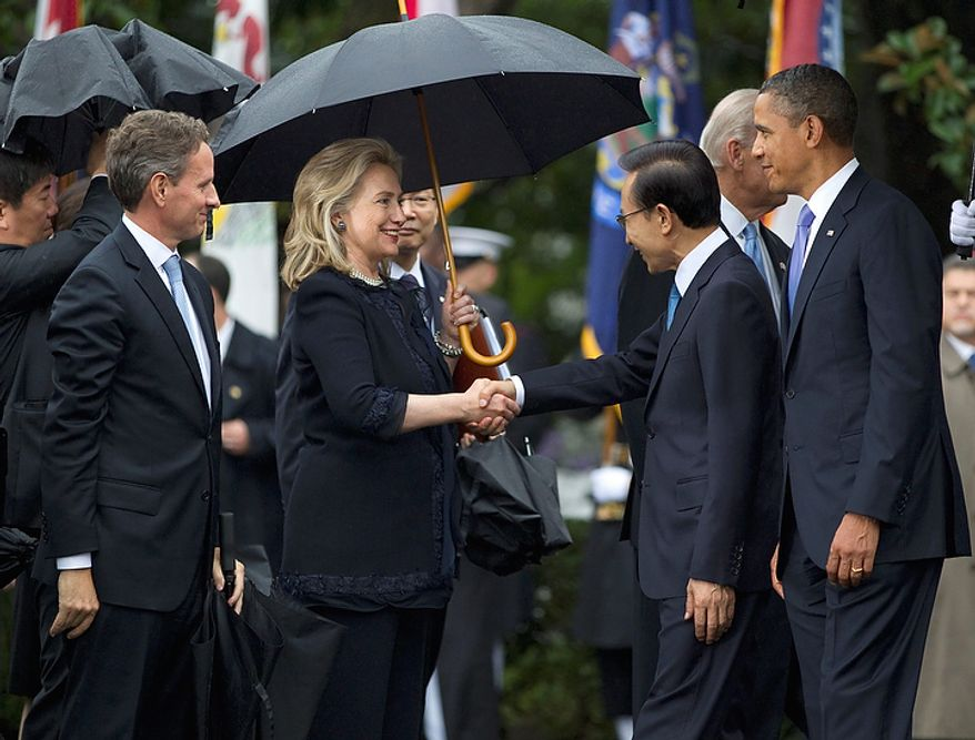 Secretary of State Hillary Rodham Clinton shakes hands with South Korean President Lee Myung-bak, accompanied by President Obama, during a state arrival ceremony on the South Lawn of the White House in Washington on Thursday, Oct. 13, 2011. At left is Treasury Secretary Timothy F. Geithner. (AP Photo/Evan Vucci)