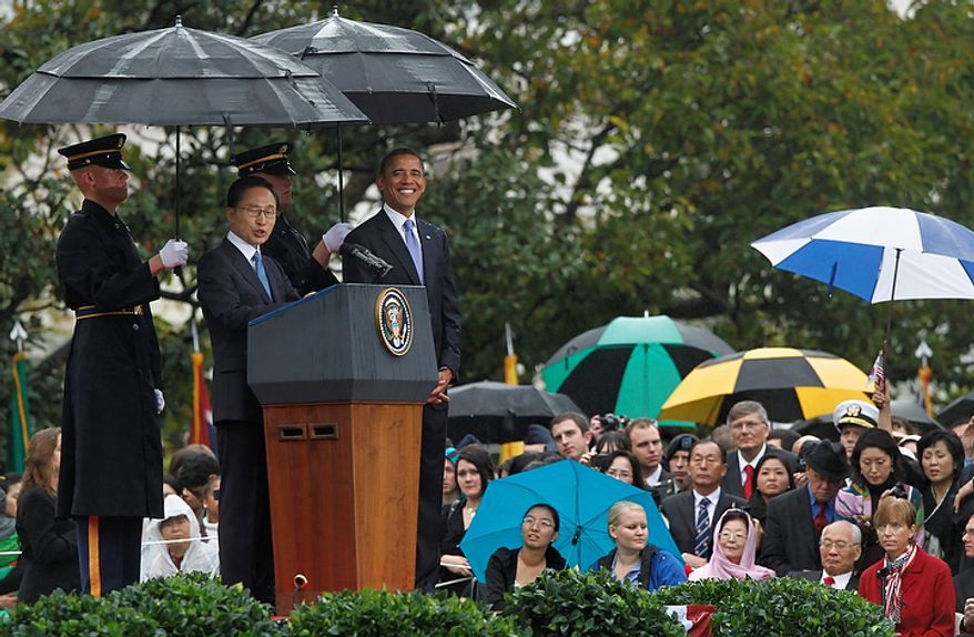 President Barack Obama smiles as he welcomes South Korean President Lee Myung-bak during a rainy state arrival ceremony on the South Lawn of the White House in Washington, Thursday, Oct. 13, 2011.  (AP Photo/J. Scott Applewhite)