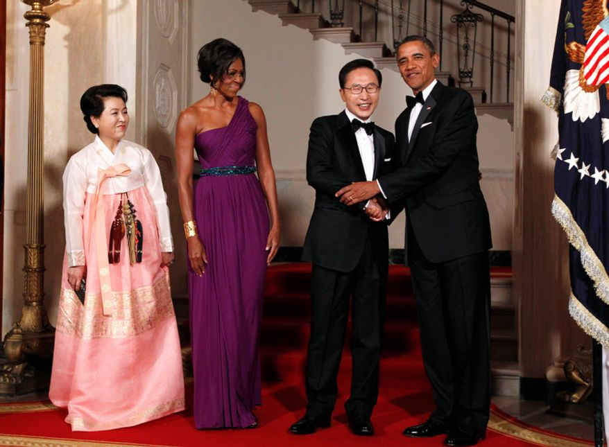 President Barack Obama and first lady Michelle Obama stand with South Korean President Lee Myung-bak and first lady Kim Yoon-ok as they welcome them to a State Dinner at the White House in Washington, Thursday, Oct. 13, 2011. (AP Photo/Charles Dharapak)