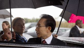 South Korean President Lee Myung-bak is escorted in the rain to his car at the Pentagon on Oct. 12, 2011, after his meeting with Defense Secretary Leon Panetta. (Associated Press)