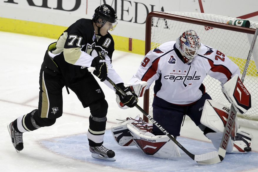 Pittsburgh Penguins' Evgeni Malkin watches as a shot by Penguins' James Neal gets past Washington Capitals goalie Tomas Vokoun on the first shot of the game. (AP Photo/Gene J. Puskar)