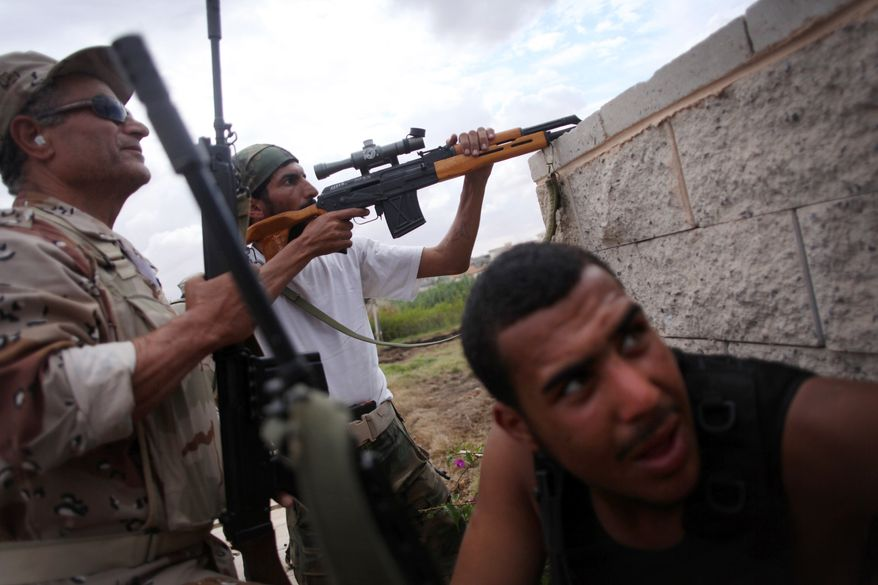 A sniper with revolutionary forces takes aim at Gadhafi loyalist positions in Sirte, Libya, on Oct. 13, 2011. (Associated Press)
