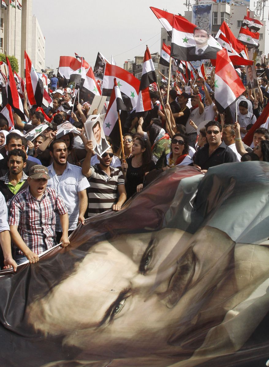 Syrian regime supporters wave a big portrait of President Bashar Assad on Oct. 12, 2011, during a demonstration in Damascus, Syria, to show their support for Assad and to thank Russia and China for blocking a U.N. Security Council resolution condemning Syria for its brutal crackdown. (Associated Press)