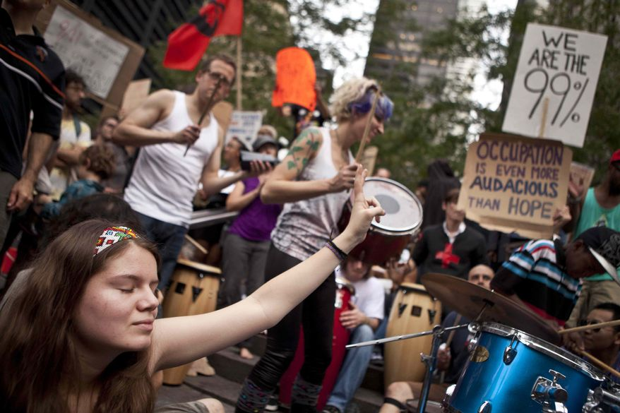 ** FILE ** A protester affiliated with the Occupy Wall Street demonstration listens to a drum circle in Zuccotti Park in New York on Monday, Oct. 10, 2011. (AP Photo/Andrew Burton)