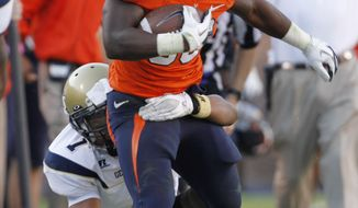 Virginia running back Perry Jones (33) tries to break the tackle of Georgia Tech safety Isaiah Johnson (1) during the second half of an NCAA College football game at Scott stadium in Charlottesville, VA., Saturday, Oct. 15, 2011. Virginia won the game 24-21. (AP Photo/Steve Helber)